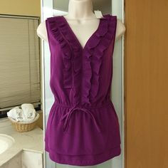 Feminine purple ruffle top size large Sleeveless purple top with ruffle accents. New with tags. Material has delicate tiny polka dots. Has double tier bottom as shown on last picture. 100% Polyester.  No Paypal. No trades. Elle Tops