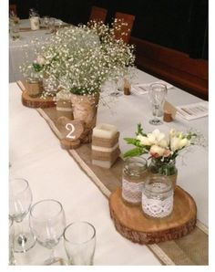 Baby's breath, hessian runners, jars and lace, Wooden discs, peonies wedding centerpiece