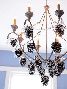 un lustre en fer forgé décoré de pommes de pin et guirlande de perles