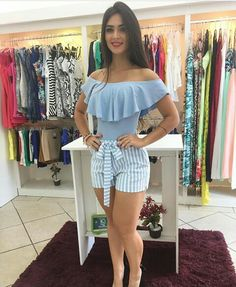 Pretty brunette blue blouse , shorts & heels in garments store