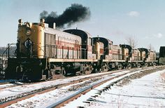 Erie Lackawanna Alco RS3 # 1010 is seen leading three other Alco RS3 locomotives while hauling a freight train in the snow at Kent, Ohio, Feburary, 1972