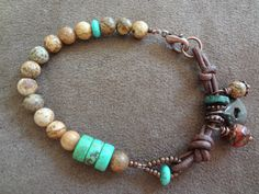 Leather & Treasures Cowgirl BraceletTurquoise by FeminineGenius- Tan and brown picasso jasper rounds, turquoise rondelles, chocolate leather, green patina mykonos ceramic washer, red picasso glass wire-wrapped dangle, chocolate seed beads. Finished with a copper lobster clasp.