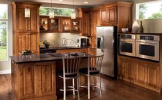 Modern rustic kitchen cabinets by KraftMaid.  The natural warmth of the outdoors is captured in this birch kitchen, finished in Praline. Modernize the look with stainless steel appliances, a glass tile backsplash and trendy pendant lighting.  Available at JustCabinets.com