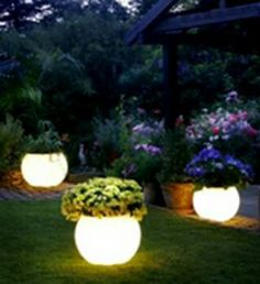 Paint flower pots with Rustoleum's Glow in the Dark paint.  Paint absorbs sunlight during the day and glows at night.  Pretty neat!