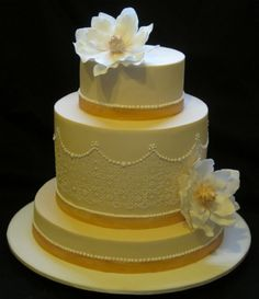 Three tiered ivory stencilled magnolia wedding cake