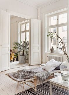 A warm, Scandinavian living room with pale colour palette, lots of texture and indoor plants - love that palm peeping in through the double doors | my scandinavian home