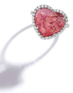 Platinum, Padparadscha Sapphire and Diamond Ring. The heart-shaped padparadscha sapphire weighing 12.94 carats, framed and accented by round diamonds weighing .65 carat, size 6.