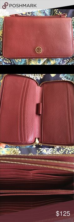 Tory Burch Organizer Wallet Burgundy leather Tory Burch organizer is large enough to hold a check book, 20 cards, cash, coins, a passport and even a smartphone.  Can be carried as a clutch with its handle. Tory Burch Bags Clutches & Wristlets