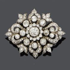 A mid 19th century diamond brooch, circa 1860 The central old brilliant-cut diamond within a single-cut diamond border, to a scroll and foliate old brilliant and single-cut diamond surround, mounted in silver and gold. Jewellery