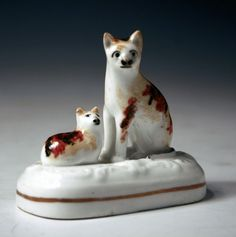 """Seated Cat with Laying Kitten. A Tortoise-Shell Coloured Cat and Kitten on a Base. Circa 1840. 2-3/4""""."""