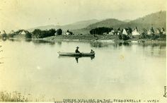 A photo of an Indian village on the Pend Oreille with two people in a boat in the foreground. Creator: Frank Palmer Creation Date: 1908 - Washington State Historical Society