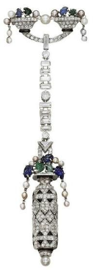 AN ART DECO MULTI-GEM LAPEL WATCH, BY BOUCHERON The diamond, onyx and black enamel stylized vase, with pearl, carved sapphire and emerald flowers, enclosing a watch with square dial, Roman numerals and blued-steel hands to the reverse, suspended from a graduated baguette-cut diamond line and twin gem-set cornucopia surmount, mechanical movement, circa 1925, 11.0 cm, with French assay mark for platinum Signed Boucheron Paris