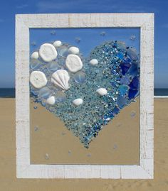 Unique beach window art by Luminosities! Lovely heart piece made of broken glass, sea glass, abalone shells, sea biscuits and shells. Measurements are 10x12