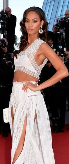 Joan Smalls completed her white Azzedine Alaïa crop top and skirt set with an envelope clutch, neutral caged sandals, and pink accented diamond statement earrings at the premier of Youth at Cannes.