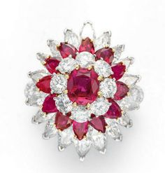 A DIAMOND AND RUBY RING, BY VAN CLEEF & ARPELS   Of bombé design, centering upon a cushion-cut ruby, trimmed by circular-cut diamonds, to the two tiered pear-shaped ruby and marquise-cut diamond surround, the shoulders decorated with circular-cut diamonds, mounted in gold and platinum  Signed Van Cleef & Arpels, N.Y