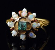 Antique gold ring, set with opal and emerald in Gothic style.Remarkable high karat gold ring. The shoulders of the hoop are decorated with foliage. The bezel raised to form a rosette set with opals and decorated with white and red enamel around a quatrefoil box set with a square emerald. The pattern is loosely based on the Gothic jewelry (mainly that of the 14th century). French, 19th century Renaissance Revival