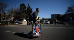A man carried a portrait of Nelson Mandela outside the hospital where the former South African President was being treated in Pretoria. AFP/ Filippo Monteforte.