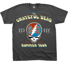 This Grateful Dead concert t-shirt is from the band's east coast leg of their 1987 summer tour, which was  performed to promote their album, In the Dark, which featured Touch of Grey, the Dead's only Top 40 single. Our 100% gray cotton tee spotlights The Grateful Dead Summer Tour 1987, with 1987 written inside the Vector lightning skull logo. Surrounding the Vector is Performing Live, East Coast and the dancing skeletons with top hats. #gratefuldead #jerrygarcia #bandtees #rockerrags