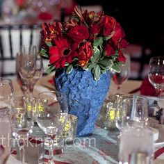 nice arrangement of different flowers in similar red hues-- The vase gives this centrepiece a pleasing variation of texture and colour.