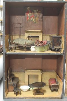 A 19th Century Naive dolls house in the form of a 3 storey building, the interior fitted 2 rooms complete with various furnishings 15 1/4\