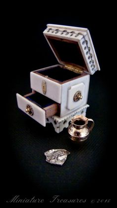 Miniature Ivory casket 21mm square by 41mm in height contains hallmarked miniature 9ct gold jug and silver roman coin fragment.