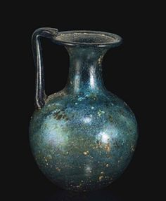 A ROMAN GLASS JUG   CIRCA 1ST CENTURY A.D.   Blue in color, free blown, the globular body on a rounded base, with a cylindrical neck and a funnel mouth, the rim folded out then in, the thin handle pulled up from the shoulders and folded over the rim