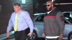 """Death Row Records founder Marion """"Suge"""" Knight, right, walks with an unidentified police officer into the Los Angeles County Sheriffs department early Friday morning in connection with a hit-and-run incident that left one man dead and another injured."""