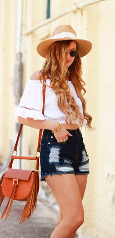 Off the shoulder crop top styled with high waisted distressed jean shorts, fringe crossbody, and circle Ray Ban sunglasses for a summer weekend outfit