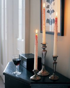 """Cast a sinister glow over any setting with a cluster of white tapers dripping with """"blood"""" (actually red candle wax). Fill a cup or a small pail with sand, and plant white candles inside so they stand upright. Light a red candle and tip it over the white candles so the wax drips down the tops and sides, being careful not to burn yourself. Let wax cool completely before removing candles from sand."""