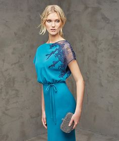 FLORIDA- Long, blue lace mermaid dress, for evening celebration, in crepe and lace. Bodice with bateau neckline, bat wing sleeves with lace appliqués and sheer effect. Narrow crepe belt with bow.