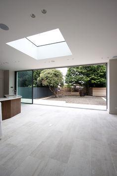 minimal windows slid open on rear extension with fixed, frameless rooflight above www.iqglassuk.com
