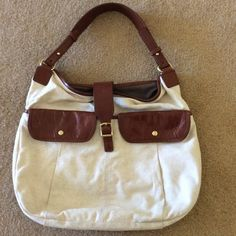 🌷J Crew Canvas and Leather Purse🌷 🌷Creamy Ivory canvas with brown leather trim🌷snaps with a buckle to close on too🌷front has two roomy pockets that snap closed🌷back has large pocket that snaps closed🌷interior is brown cotton with no flaws and zip pocket as well as two other pockets for cell phone or any item you need at your fingertips🌷Great shape. Only slight flaw is shown in picture 4 of little scratch of leather flap which was there when purchased. Doesn't detract at all🌷 J. Crew…