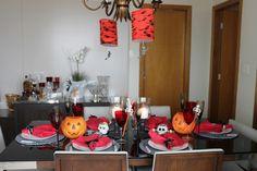 Decoração de mesa para o Halloween em vermelho e preto usando acessórios temáticos.