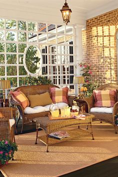 This 35-foot-long by 9-foot-deep back porch respects Southern porches of the past by using traditional shading devices such as a trellis at one end. Comfortable rattan chairs, cushioned in red, yellow, and green, add cheer to this outdoor living room. Ceiling fans help cool the space during sultry summer days, while three copper-finish lanterns contribute to the ambience.  Read more about the Abberley Lane Idea House