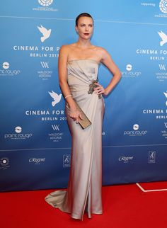 Charlize Theron wore a Gucci one of a kind pale silver strapless satin gown with silver embellished applique detail at the waist and grey satin clutch with crystal beading to the the Cinema For Peace Gala 2013 during the 63rd Berlinale International Film Festival at the Waldorf Astoria Hotel in Berlin on February 9, 2013.