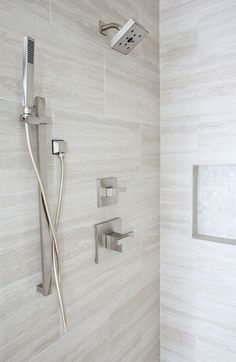 Beautiful shower by Jennifer Reynolds Interiors. Custom shower niche with handheld spa showerhead. Marble vein-cut slab, Brizo fixtures.