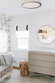 Neutral Nursery with gray changing table, wallpaper, and black out roman shades