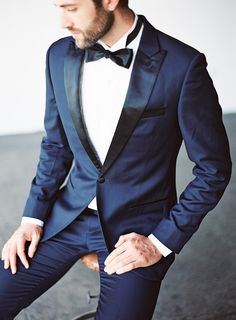This groom looks svelte and smooth in a midnight tux that puts a twist on the old classic, with black lapels and a matching bow tie.
