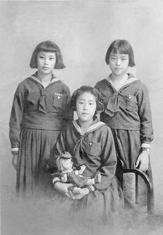 Commemorative photo Japanese students -in school uniforms, one holding a blood bed doll. Japan - October 6, 1940.