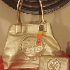 TORY BURCH METALLIC STACKED LOGO TOTE NWT TORY BURCH METALLIC GOLD STACKED LOGO TOTE. ALL OFFERS WELCOMED USING OFFER BUTTON. THANKS  Metallic pebbled leather.  Studded detail with leather logo.  Canvas lining.  Round detchable mirror.  Double leather handles with 8″ drop.  Magnetic snap closure.  Interior zip and two additional open pockets.  17 1/4″ W x 13 Tory Burch Bags Totes
