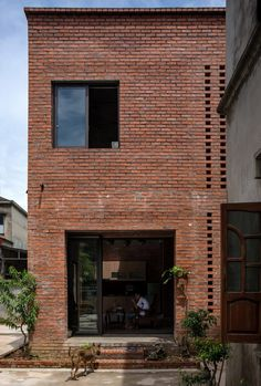 The two-storey, 75 square metres home was built with a frame of reinforced concrete and clad in red brick, which are also used exposed throughout the interiors. Flood Areas, Water Collection System, Vietnam, Brick Architecture, Temporary Architecture, Residential Architecture, Wall Exterior, Construction Process, Brick Construction