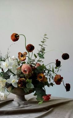 I love the sense of whimsy that ranunculus always bring to the table.This asymmetrical garden mixed arrangement in a footed urn is no exception. Ikebana, Deco Floral, Arte Floral, Floral Design, Fall Wedding Flowers, Floral Wedding, Floral Centerpieces, Wedding Centerpieces, Centrepieces
