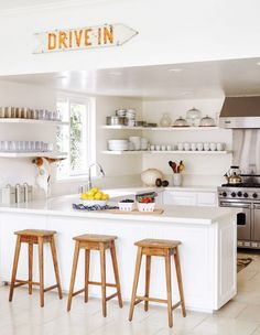 Bright white kitchen with an eclectic sign, floating shelves, and wood stools
