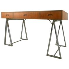 View this item and discover similar for sale at - Unusual teak desk with simple modern design set on two polished chrome saw horse legs. Three drawers with sculpted handles, wide surface area with warm Modern Desk, Writing Desk, Table Furniture, Polished Chrome, Office Desk, Teak, Vintage Desks, Drawers, Floor Plans