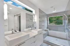 Master Bathroom. Lots of natural light is welcomed in through the window in the shower as well as the transom above the vanity mirror. Floating custom vanity with quartz counter and 2 vessel sinks. Full tile walk in shower with bench, niche, and modern chrome plumbing fixtures.