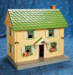 """17"""" (43 cm.) American Wooden Two Story  Dollhouse by Schoenhut 600/900  17"""" x 17"""" x 11""""d. Wooden framed two story dollhouse with green shingled roof, chimney, six windows, green painted tin panes, pressed cardboard shutters, and porch overhang above paned front door. The front opens for access to the four interior rooms. Excellent condition. American, Schoenhut, circa 1910, rare small size in wonderfully preserved condition."""