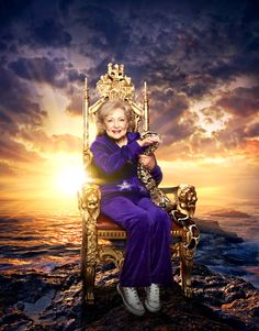"""Betty White seated as royalty and dressed for her """"I'm Still Hot"""" video, a purple velour track suit. Holding Jason, a boa constrictor from the LA Zoo"""