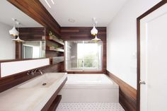 """In order to give the redesign a seamless feel, Brigham and Archuleta carried the use of wood throughout the room—including the shower. Archuleta researched types of wood that can withstand a high-moisture environment, and the most visually appealing was coastal redwood. He came across an unlikely source of reclaimed redwood: old pickling vats from a company called Trestlewood.   Experience in working with reclaimed wood taught Archuleta that """"wood that's been exposed to liquid for long…"""