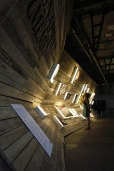 Angled wall made from wooden planks with mounted graphics.