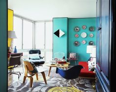 Conteporary living room with patterned rugs, a red sofa, blue Eames chair and turquoise walls with decorative plates